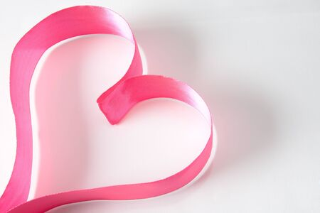 Form of heart made up of pink ribbon over white background photo