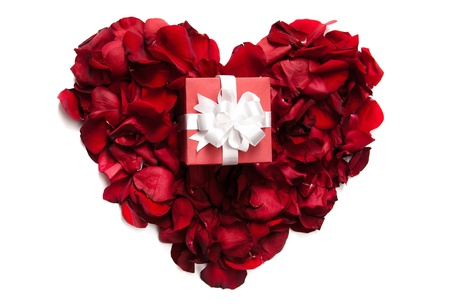 Red rose petals making up heart with small giftbox on it photo