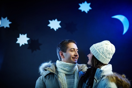 Portrait of happy couple looking at one another with moon and stars above their heads photo