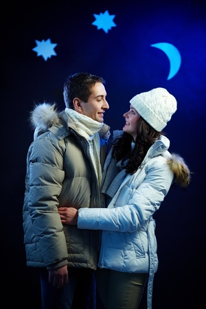 winter couple: Portrait of happy couple looking at one another with moon and stars above