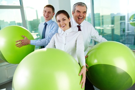Portrait of joyful business partners with big balls looking at camera in office photo