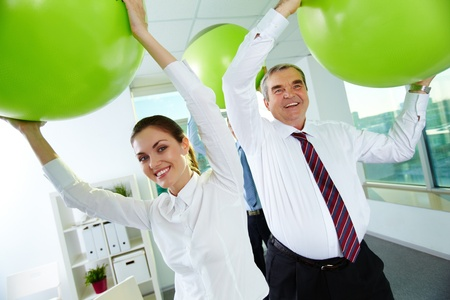 Portrait of joyful business partners playing with big balls in office photo