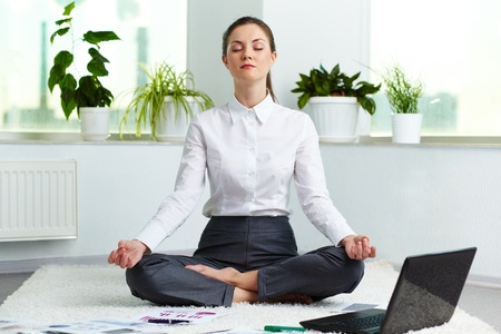 Portrait of attractive white collar worker meditating in office photo