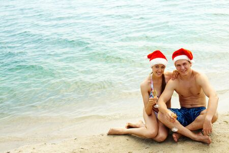 Portrait of attractive couple in Santa caps looking at camera on the beach photo