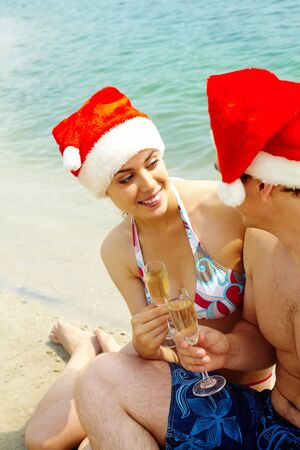 Portrait of attractive couple in Santa caps celebrating xmas on the beach photo