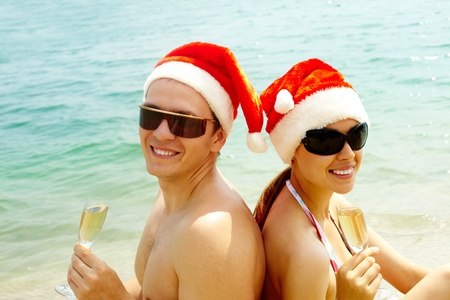 Portrait of attractive couple in Santa caps and sunglasses looking at camera on the beach photo