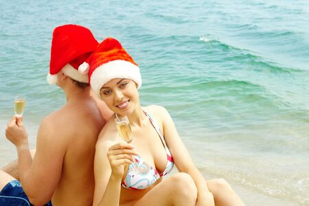 Portrait of female in bikini and Santa cap holding champagne flute and looking at camera on the beach with her husband behind photo