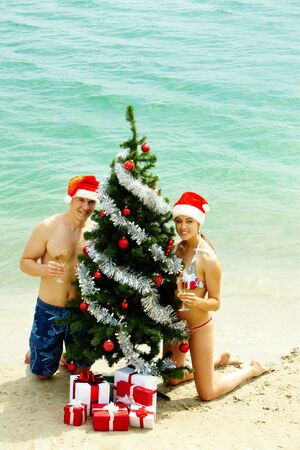 beach happy new year: Portrait of happy couple in Santa caps holding champagne flutes and looking at camera with decorated firtree near by Stock Photo