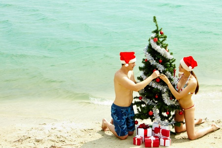 beach happy new year: Portrait of happy couple in Santa caps decorating xmas firtree on the beach Stock Photo