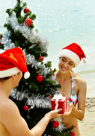 Portrait of happy couple in Santa caps near xmas firtree on the beach photo