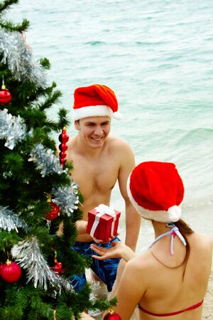 Portrait of happy man in Santa cap giving giftbox to his wife near xmas firtree on the beach photo
