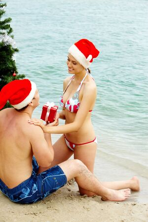 Portrait of happy woman in Santa cap giving giftbox to her husband near xmas firtree on the beach photo