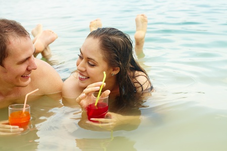 restful: Portrait of restful couple holding glasses with fresh juice while relaxing in water