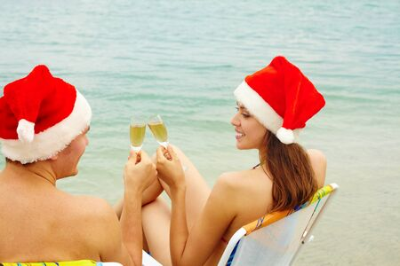 Portrait of happy couple in Santa caps toasting with champagne and looking at one another on the beach photo