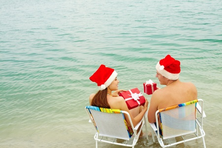 beach happy new year: Portrait of happy couple in Santa caps holding giftboxes and looking at one another on the beach
