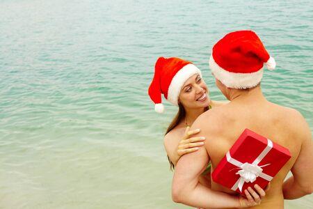 detras de: Retrato de mujer feliz en la tapa de Santa abrazando a su marido mientras él escondido de regalo a sus espaldas Foto de archivo
