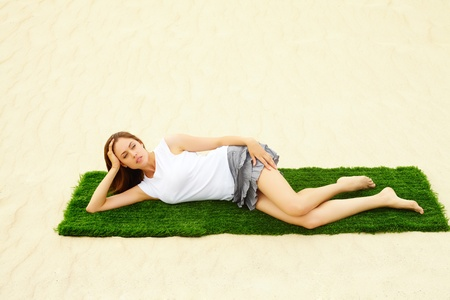 Portrait of pretty young lady relaxing on green grassland in the middle of sandy beach during vacation photo