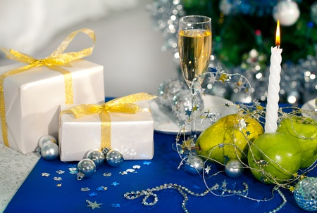 new year eve beads: Image of holiday table with flute of champagne, fruits, gifts, burning candle and decorations on it