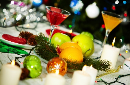 Image of holiday table with cocktails, fruits, burning candles and decorations on it photo