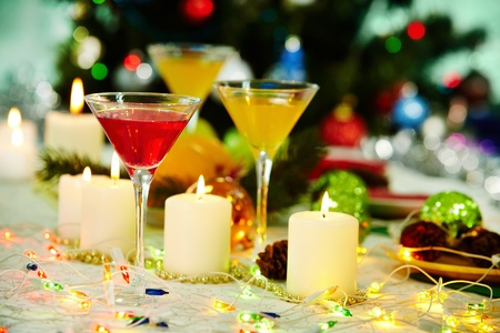 new year eve beads: Image of holiday table with cocktails, burning candles and decorations on it