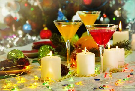 image of holiday table with cocktails burning candles and