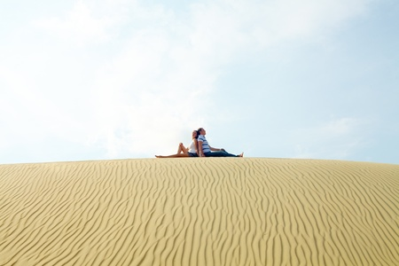 restful: Image of restful couple sitting on sandy beach during vacation