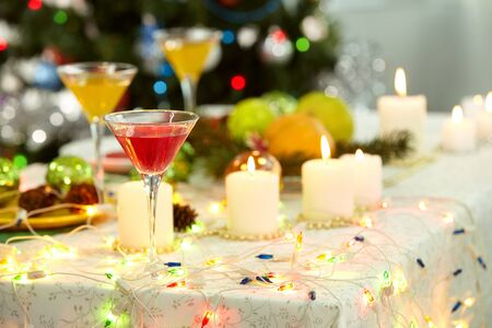 Image of holiday objects: cocktails, burning candles and Christmas decorations photo