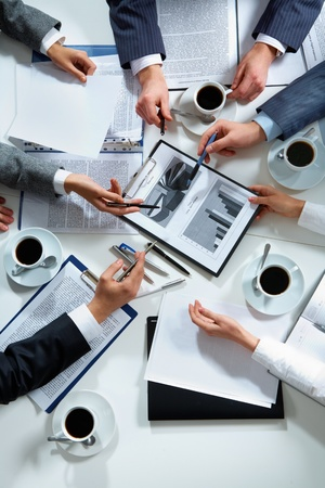 project planning: Close-up of business team hands over papers during discussion of a new project