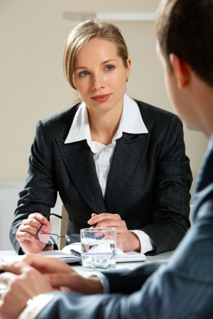 Image of young female looking at her partner while listening to him at meeting photo