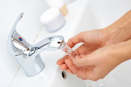 lavandose las manos: Close-up de la mano del hombre se lavan bajo una corriente de agua pura del grifo Foto de archivo