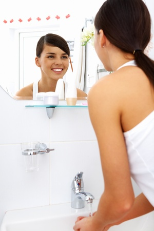 Image of pretty female looking in mirror while washing her hands in the morning photo