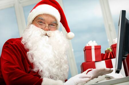 Portrait of Santa Claus in front of computer monitor looking at camera Stock Photo - 11268462