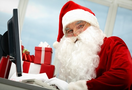 Portrait of Santa Claus in front of computer monitor looking at camera photo