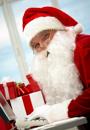 Portrait of Santa Claus typing and looking at camera photo