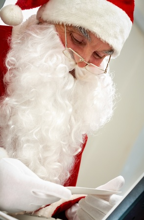 Santa holding Christmas letter and looking at it photo