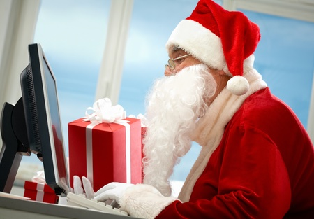 Portrait of Santa Claus in front of computer monitor with gifts photo