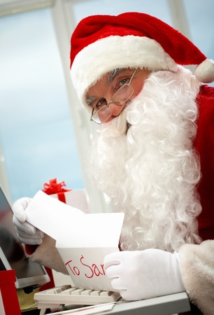 Santa holding Christmas letter and looking at camera photo