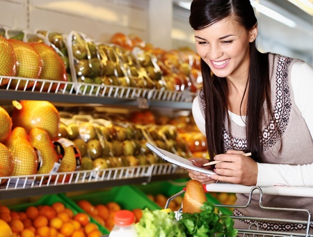 veg: Image of pretty woman choosing products in supermarket with list of things to buy Stock Photo