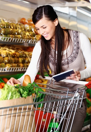 supermarket cart: Image of pretty woman choosing products in supermarket with list of things to buy Stock Photo