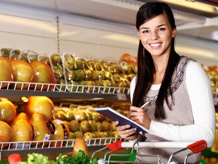 Image of pretty woman looking at camera while choosing products in supermarket photo