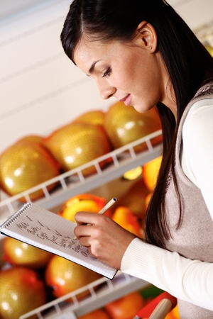 Image of pretty woman ticking what she has bought in supermarket Stock Photo - 11268434