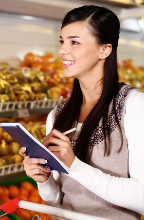 Image of pretty woman ticking what she has bought in supermarket Stock Photo - 11268452