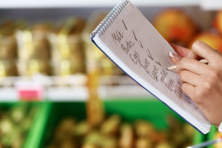 Image of female hand with pen holding product list while buying goods in supermarket Stock Photo - 11268430