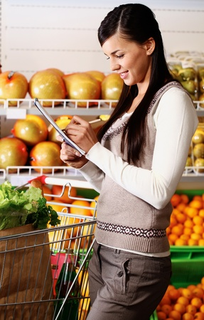 Image of pretty woman ticking what she has bought in supermarket Stock Photo - 11268455