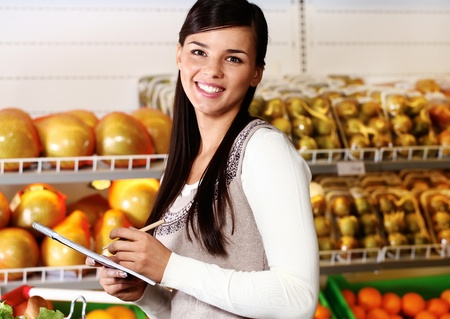 Image of pretty woman looking at camera in supermarket photo
