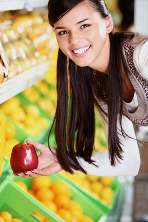 Image of happy woman with fresh apple in hand looking at camera in supermarket photo
