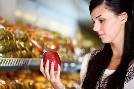 Image of young woman with fresh apple in hand looking at it in supermarket Stock Photo - 11268445