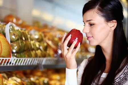 olfato: Imagen de una mujer joven con la manzana fresca en la mano que olía en el supermercado