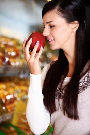 Image of young woman with fresh apple in hand smelling it in supermarket photo