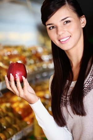 Image of happy woman with fresh apple in hand looking at camera in supermarket Stock Photo - 11268453